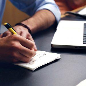 Persona escribiendo en una libreta junto a un laptop